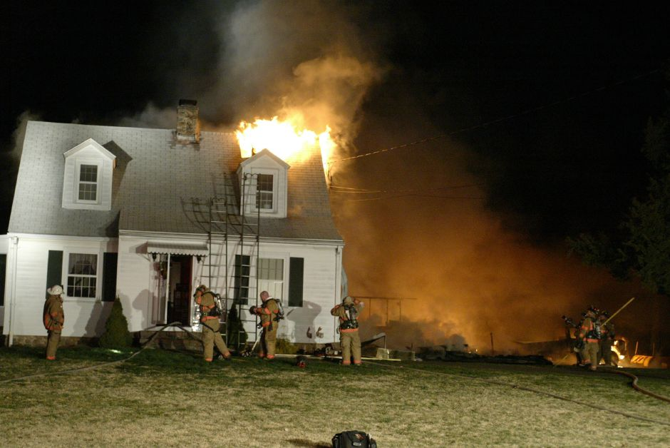 Firefighters focus there attention on this house at 253 New Cheshire Rd. in Wallingford after a fire broke out in the detached garage around 10:30 p.m. and spread to the house on April 11, 2006. The garage, burning at left, was totally destroyed and the house suffered extensive damage.