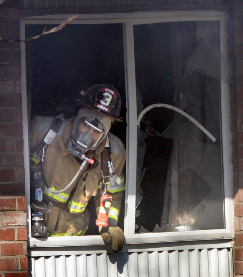 A Meriden firefighter observes from the second floor window of an apartment which caught fire at 11:06 a.m. Tuesday morning at Hillside Gardens on Hall Ave. in Meriden February 17, 2009. The fire occurred in an apartment located on the east side of the Carabetta managed complex. (dave zajac photo)