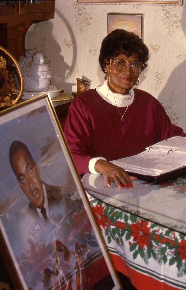 RJ file photo - Rhudean Raye sits at her kitchen table with a picture of Martin Luther King Jr. Jan. 5, 1994.