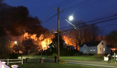 This photo provided by WFSB-TV shows a fire behind a house, Wednesday, May 2, 2018, in North Haven, Conn. A Connecticut woman