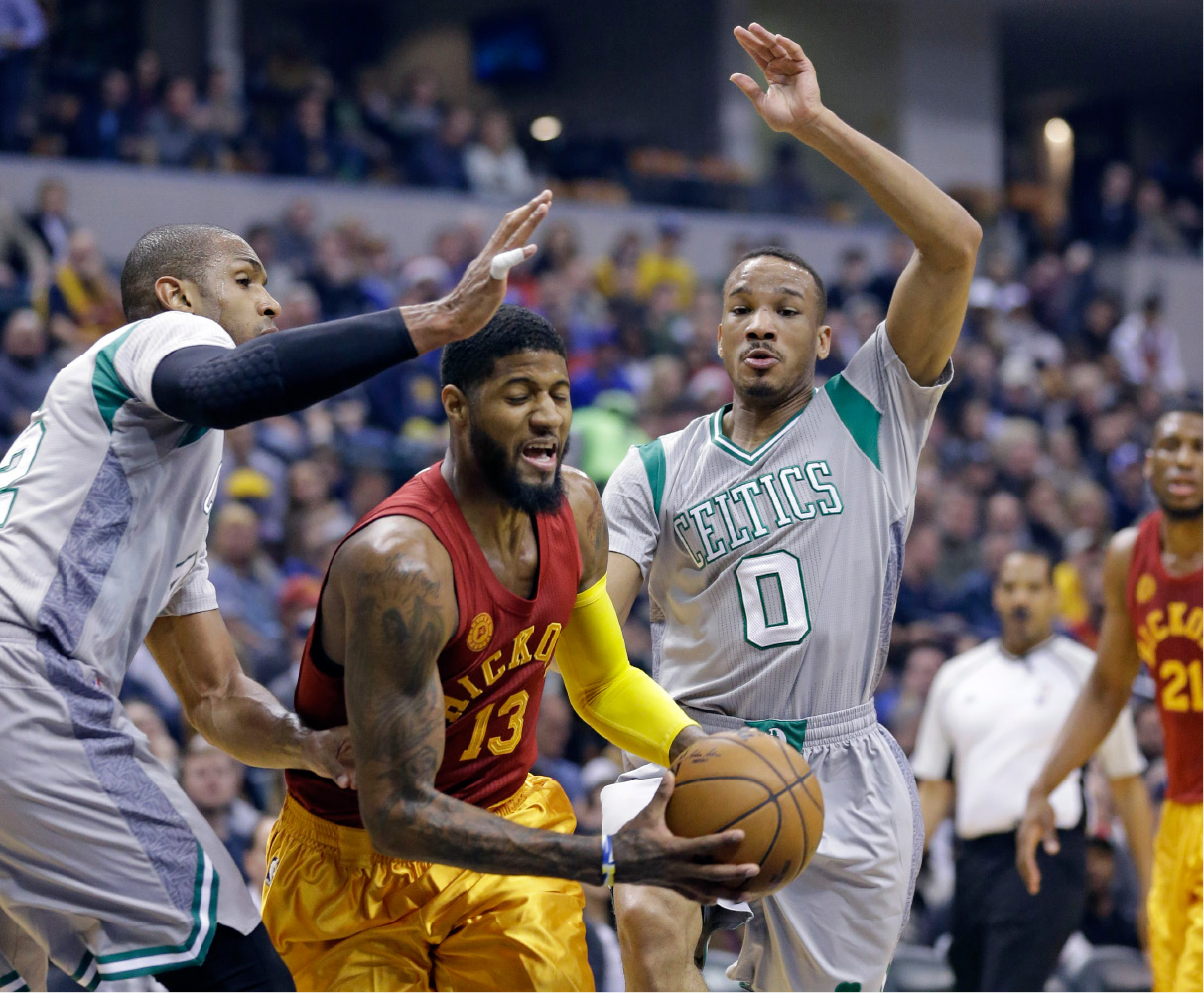 Indiana Pacers forward Paul George (13) cuts between Boston Celtics center Al Horford (42) and guard Avery Bradley (0) during the first half of an NBA basketball game in Indianapolis, Thursday, Dec. 22, 2016. (AP Photo/Michael Conroy)