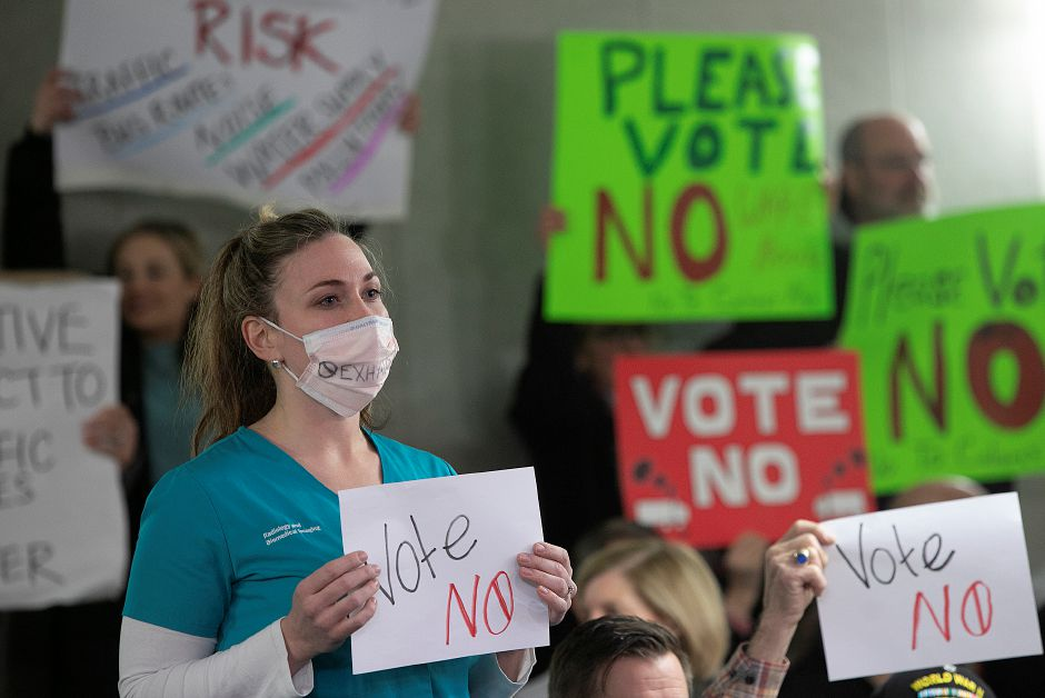Juliette Buccilli, of Wallingford, wears a mask while protesting development of the former Bristol-Myers Squibb property during Monday night