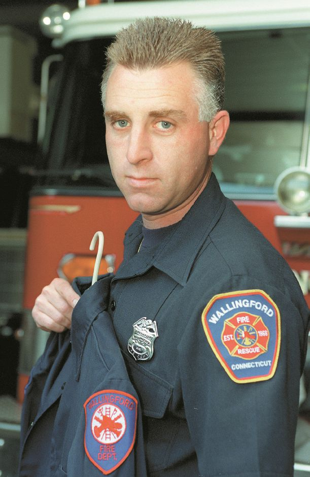 RJ file photo - Wallingford firefighter Walter Schrenker, an aspiring artist, wears a shirt with the new patch he helped design. He is holding a shirt with the old patch, May 1998.