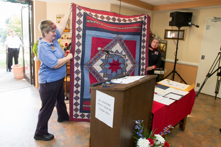 Janice Dougherty and Cindy Guendert open a quilt Friday during a Quilts of Valor ceremony at The Summit at Plantsville in Plantsville October 27, 2017 | Justin Weekes / For the Record-Journal