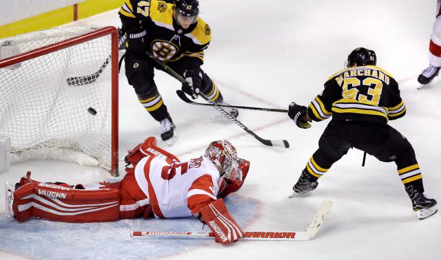 Boston Bruins left wing Brad Marchand (63) flicks a backhand shot over Detroit Red Wings goaltender Jimmy Howard (35) for the game-winning goal during the overtime period of an NHL hockey game in Boston, Tuesday, March 6, 2018. Marchand notched a hat trick in the Bruins