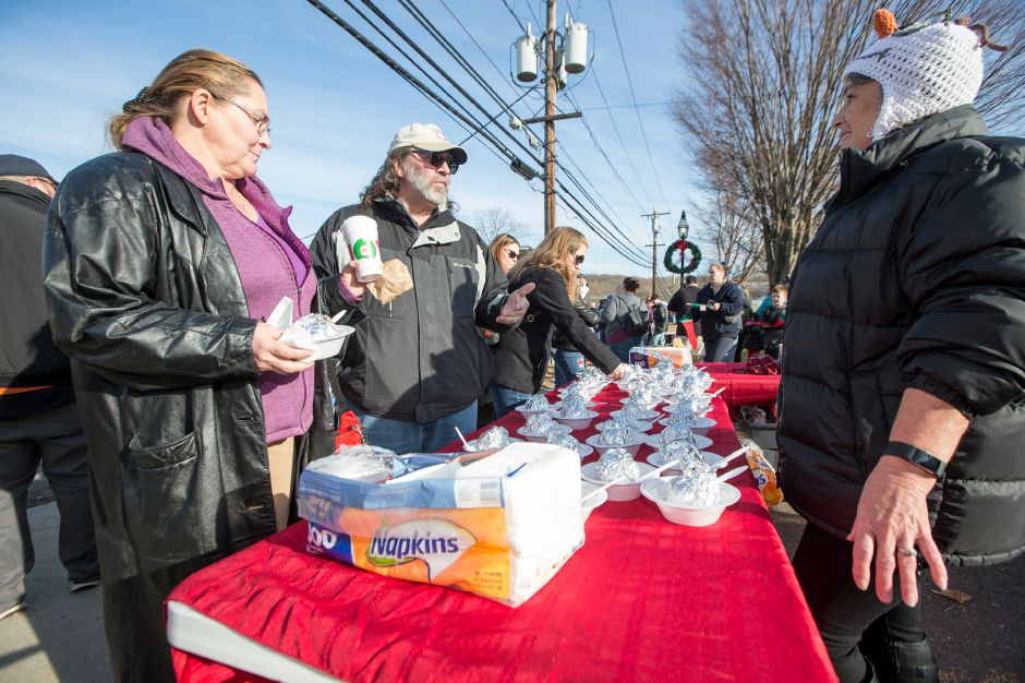 Donna and Ricky Graham try the baked apples from Debbie Haberli Saturday during Christmas in the Village on Main Street in South Meriden December 1, 2018 | Justin Weekes / Special to the Record-Journal