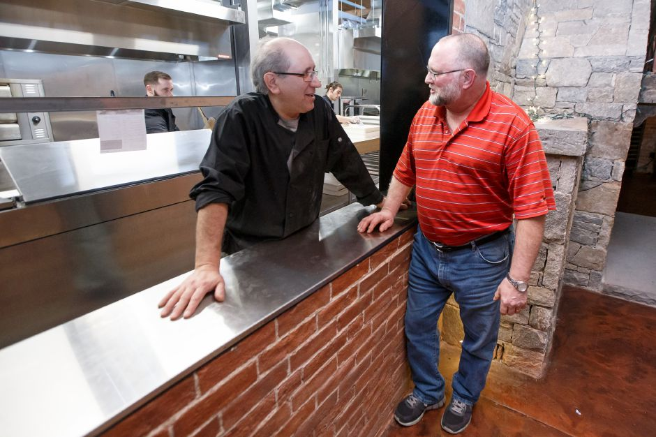 Bob Vasil of Berlin right compliments co-owner Vinny Crudele on his pizza Saturday at Sauced at Kinsmen in the Kinsmen Brewery in Southington February 10, 2018 | Justin Weekes / Special to the Record-Journal