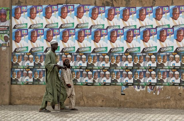 A child leads a blind man as they walk past a wall of campaign posters in Kano, in northern Nigeria, Saturday, Feb. 16, 2019. A civic group monitoring Nigeria
