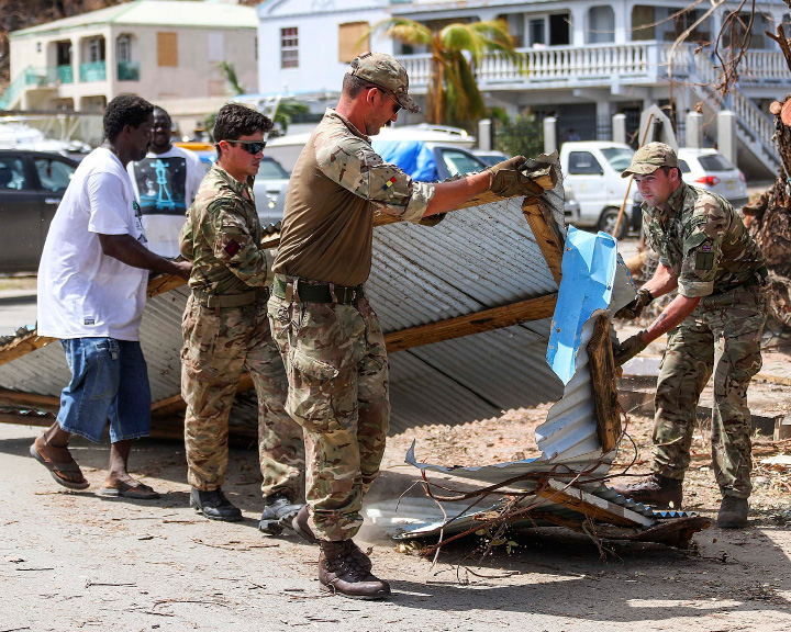 In this undated photo provided on Tuesday, Sept. 12, 2017 by the British Ministry of Defence, Army Commandos deliver aid and provide support to British Virgin Islands communities on the island of Tortola. Britain sent a navy ship and almost 500 troops to the British Virgin Islands, Anguilla and the Turks and Caicos islands. (MOD via AP)