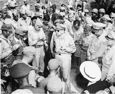 Gen. Douglas MacArthur, center, talks to reporters after his arrival, August 28, 1945 at Atsugi Airport, near Tokyo, Japan, from Manila. (AP Photo)