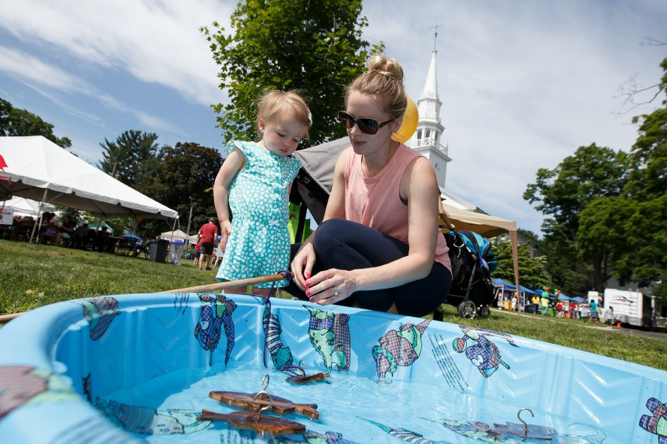 Clara Chaback 1 gets help from mom Carla with a fishing pole in the kids area Saturday during the 81st Annual Cheshire Strawberry Festival and Craft Fair on the Town Green in Cheshire May 31, 2016 | Justin Weekes / Special to the Record-Journal