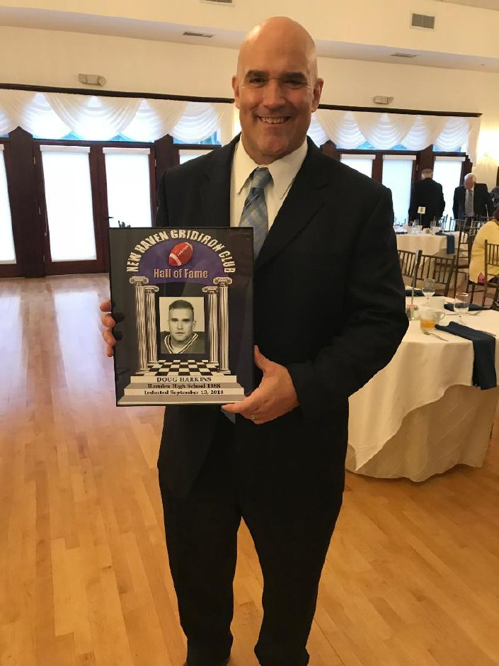 Durham Middlefield Falcons defensive coach Douglas Harkins proudly displays his Hall of Fame plaque.