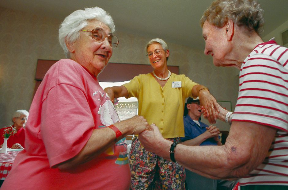 RJ file photo - Jackie Iverson, center, a recreational therapist, dances with visitor Jennie DeLucia, left and resident Halen Hlavac, right, durign the Italian Fest at Regency House, August 1998.
