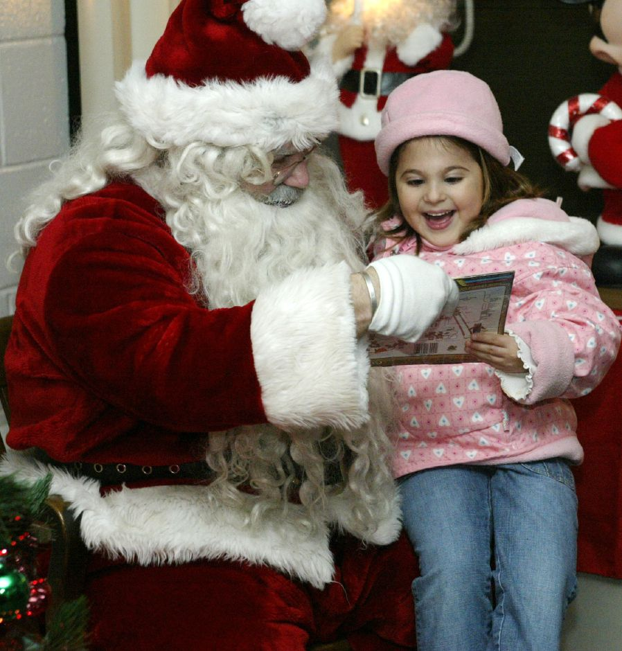 Juliette Lord, 4, of Southington, gets an early Christmas gift from Santa Claus at the Southington Fire Department Company 2 in Plantsville on Dec. 1, 2005. Santa was visiting the station for the 15th Annual Christmas in the Village event.