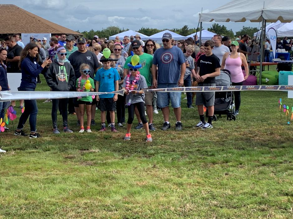 Emelia Brandi cuts the ribbon before the start of the Take Steps Shoreline Walk at Hammonasset Beach State Park in Madison. Photos by Everett Bishop, The Citizen