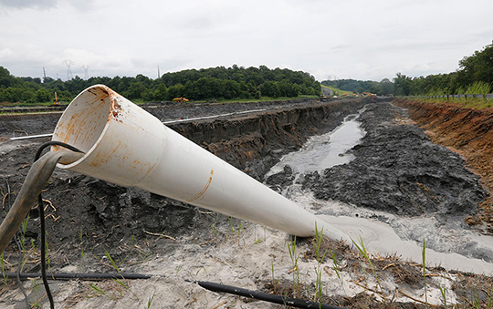 A drain pipe sticks out of a coal ash retention pond at the Dominion Power