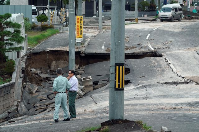 Men stand on an earthquake-damaged street in Kiyota, outskirts of Sapporo city, Hokkaido, northern Japan, Friday, Sept. 7, 2018. A powerful earthquake hit wide areas on Japan