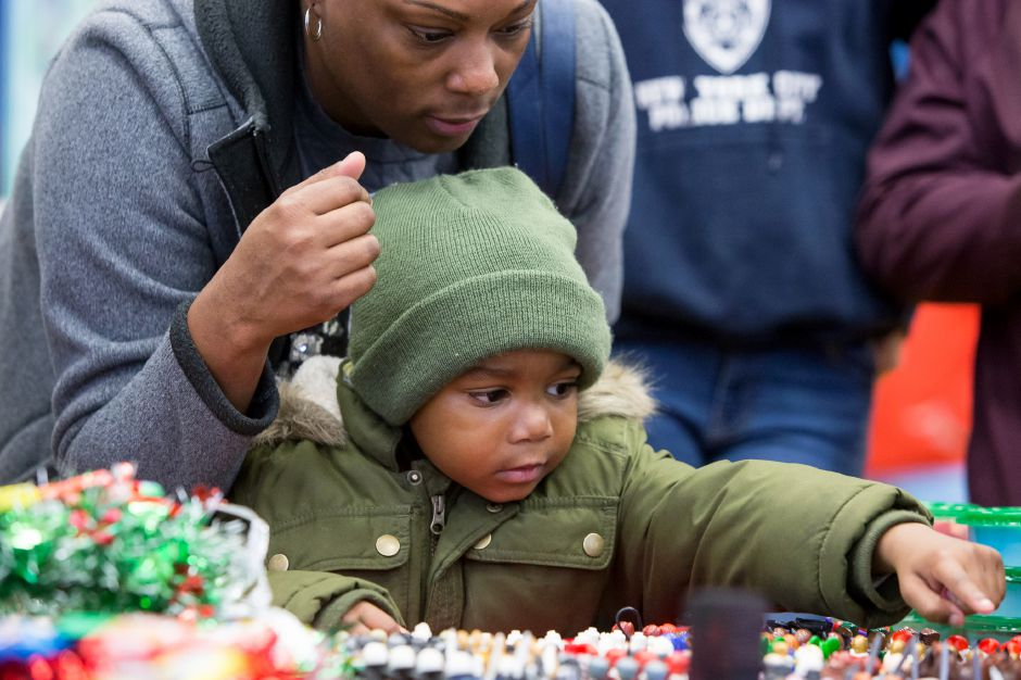 Dorian Tatum 4 picks out a Lego minifig with help from mom Nataya at a vendor booth inside Hanover Elementary School Saturday during Christmas in the Village on Main Street in South Meriden December 1, 2018 | Justin Weekes / Special to the Record-Journal