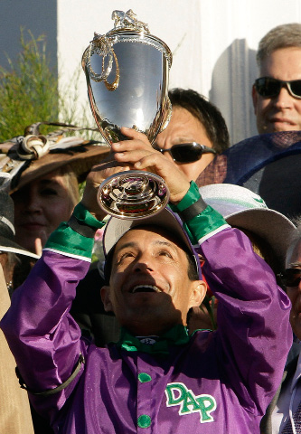 Victor Espinoza holds the trophy after riding California Chrome to victory in the 140th running of the Kentucky Derby horse race at Churchill Downs Saturday, May 3, 2014, in Louisville, Ky. (AP Photo/Garry Jones)