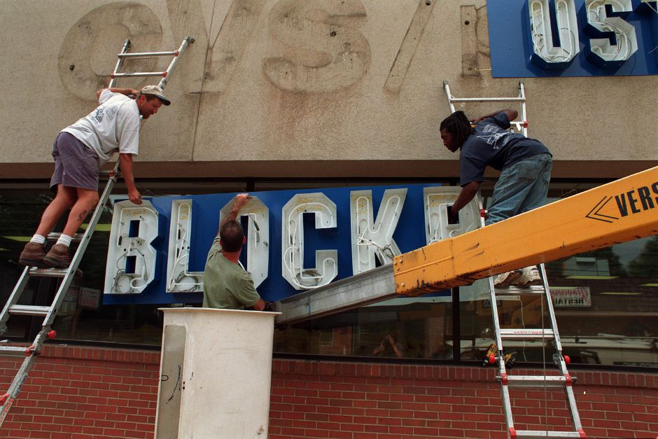 Workers install a new sign on an old building on Main Street in Southington Aug. 11, 1999. The sign is for the Blockbuster video rental store.