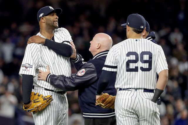 New York Yankees trainer Steve Donohue, center, checks on pitcher CC Sabathia during the eighth inning of Game 4 of baseball