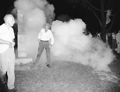 An unidentified man runs through the Anderson County courthouse yard when police officials threw tear gas to disperse a large crowd which had gathered in the same place as last night when violence flared in Clinton, Tennessee, Sept. 1, 1956. Many citizens of Clinton volunteered for the police force. About 100 state police rushed to scene when the crowd started pushing in on the police. (AP Photo)