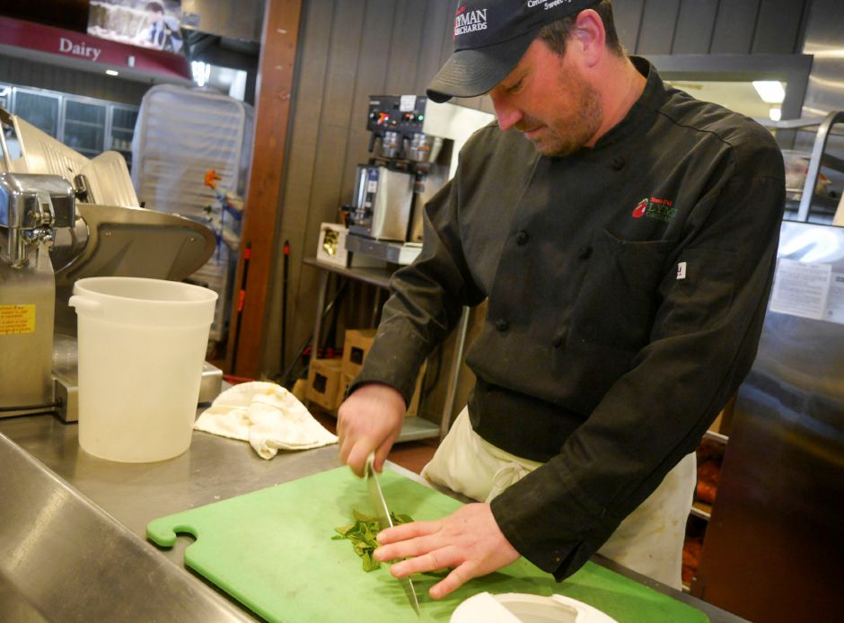 Apple Barrel sous chef Ryan Quinn chops mint leaves for a tabouli recipe on March 11 in Middlefield, in preparation for the reopening of the Lyman Orchards store this Saturday, March 16. | Bailey Wright, Record-Journal