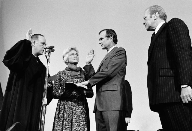 FILE - George H.W. Bush, center, is sworn in as director of the Central Intelligence Agency by Supreme Court Associate Justice Potter Stewart, left, as Barbara Bush and President Gerald Ford, right, look on at CIA headquarters in Langley, Va. Bush died Friday, Nov. 30, 2018, at the age of 94. Bush was largely known for his work in public office, from his time as a Texas congressman and CIA director to his years in the White House as president and Ronald Reagan