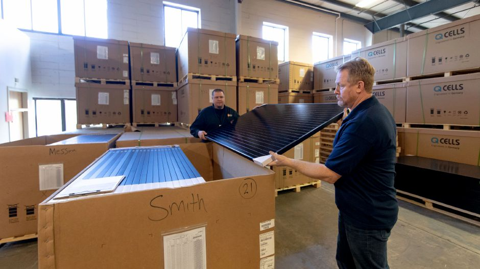 Employees at Trinity Solar remove a solar panel for Democratic Senator Chris Murphy, center, Lt. Gov. candidate Susan Bysiewicz and Democratic Gubernatorial candidate Ned Lamont to inspect. The Democrats toured the company and spoke about the importance of clean energy on Oct. 25, 2018.