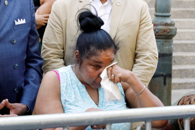 Esaw Snipes, widow of chokehold victim Eric Garner, wipes her eyes during a news conference outside the U.S. Attorney