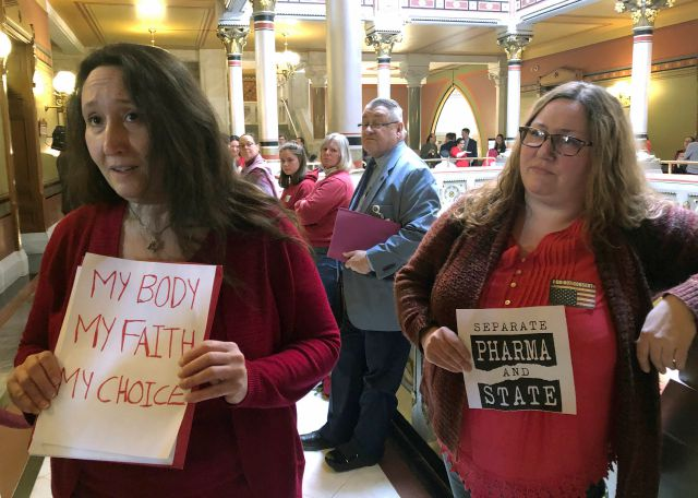 FILE - In this March 13, 2019 file photo, mothers Ariana Rawls, left, of Stratford, Conn., and Shannon Gamache, right, of Ashford, Conn., talk to reporters about legislative efforts to change the state