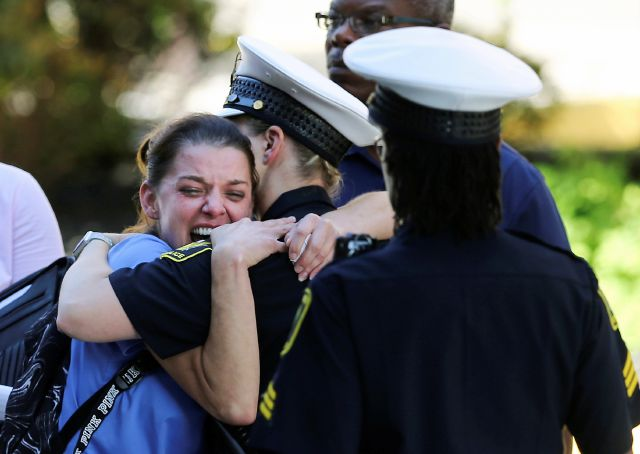 A woman is comforted by authorities stationed outside the University of Cincinnati Medical Center