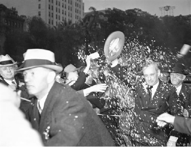 Los Angeles greeted Gov. Alf M. Landon of Kansas, Republican presidential nominee in holiday spirit as he rode through the streets. Here he is trying ineffectively to dodge confetti aimed him as he entered a hotel in Los Angeles on Oct. 21, 1936. (AP Photo)