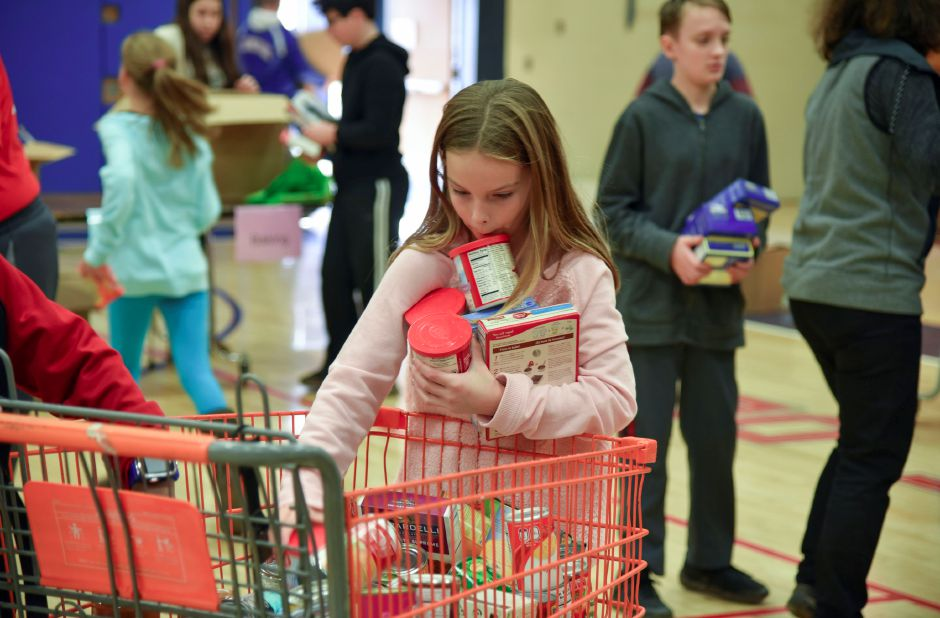 Aubrey Christopher, 10, helps sort food donations during the 13th annual Community Round-up in Durham and Middlefield on Saturday, Dec. 1, 2018. The event collected more than 13,000 food items and about $3,500 to go to Durham and Middlefield Social Services, and Amazing Grace in Middletown. | Bailey Wright, Record-Journal