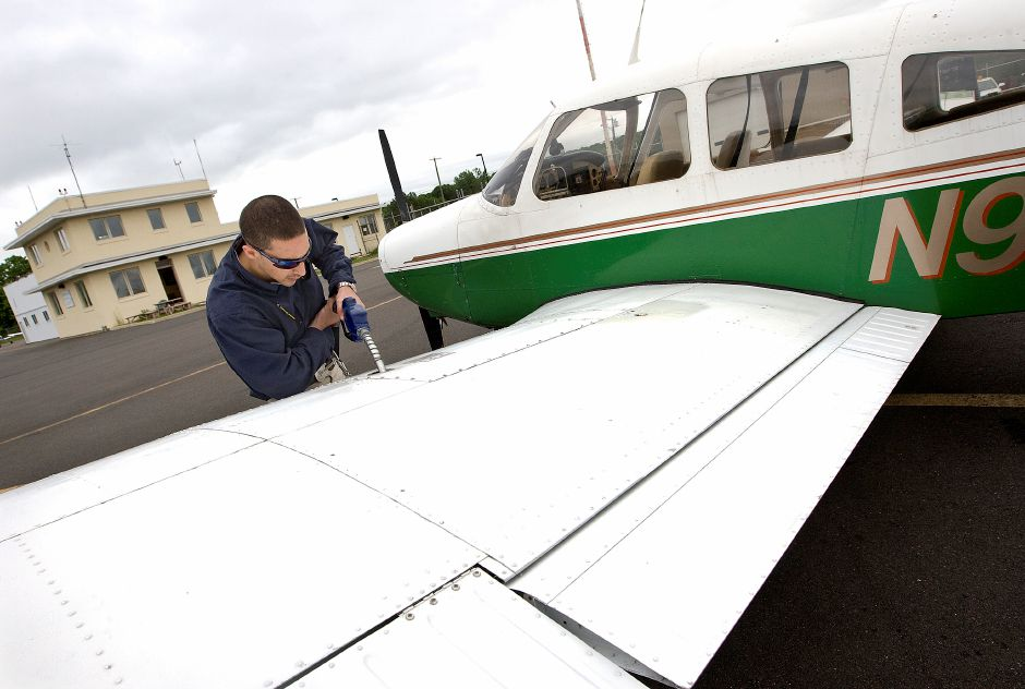 Flight Instructor, Mike DiFiore, of Middletown, fuels up a Piper Warrior at Meriden-Markham Airport in preparation for a return flight to Hartford-Brainard Airport, Wednesday, May 28, 2014. Meriden-Markham strives to offer the lowest fuel price in the state of CT. | Dave Zajac / Record-Journal