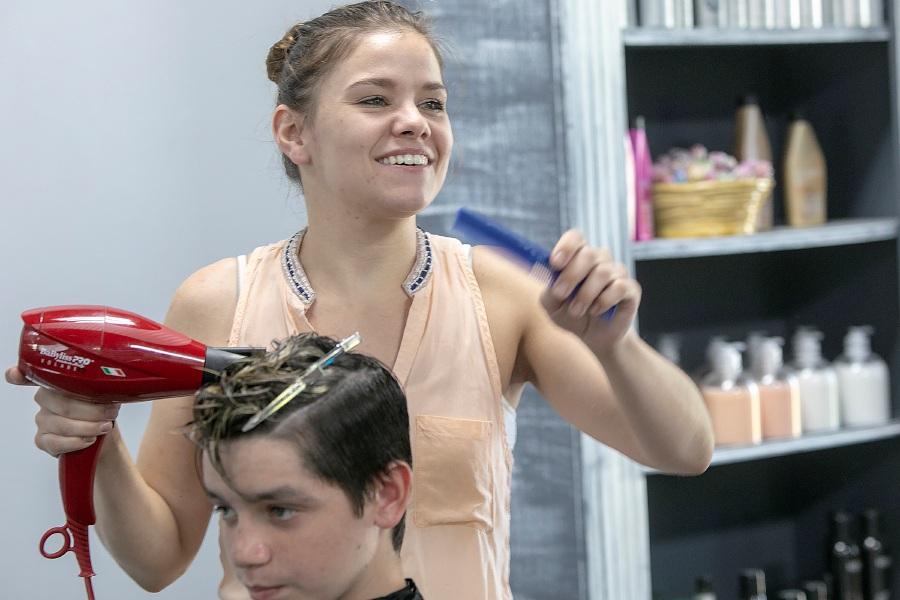 Marguerite Swan, owner of Salon Margo, smiles while giving a haircut to Noah Tamayo, 13, of Southington, Friday, August 24, 2018. Swan moved her business from Plainville to just over the town line to 1079 Queen St. Dave Zajac, Record-Journal