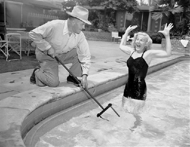 "This shocking picture shows Joan Wills screaming as she comes within range of a zone in the water electrified by the ""Neptune's Fork"" held by Henry T. Burkey in Hollywood, Calif., where he lives, Aug. 22, 1952. Burkey, an electrical engineer, designed the gadget for use by victims of shipwrecks of air crashes over shark-infested waters. The device consists of two electrodes connected to batteries in the waterproof handle. The electrodes create an electrified zone in the water to repel attacking fish. He says the device is shockproof to the user.  (AP Photo/Don Brinn)"