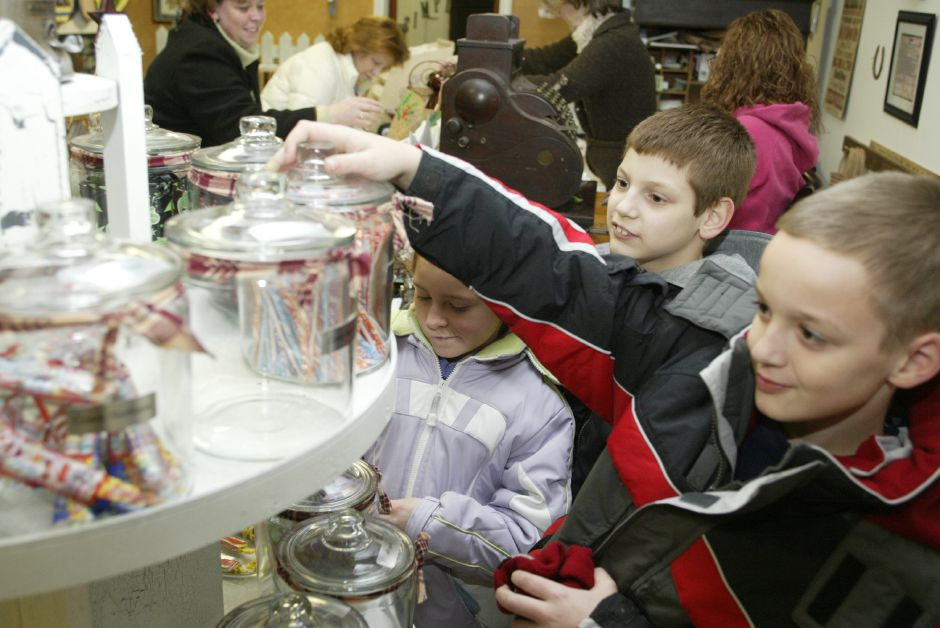 "Tyler Berube, 10, of Meriden, right, Matt Sorbello, 10, of Southington, second from right, and Taylor Javie, 8, of Meriden, center, pick out some candy at The Simple Life, a shop in dowtown Plantsville on Dec. 1, 2005. While children were attracted to the ""penny"" candy rack, The Simple Life was serving free cookies to customers and guests while they shopped during the 15th Annual Christmas in the Village. [Note: ""Penny"" is the store owner"