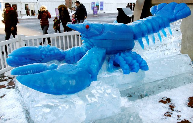 People walk past a blue lobster ice sculpture outside the New England Aquarium as the temperature hovers in the low teens, Thursday, Dec. 28, 2017, in Boston. The National Weather Service said there