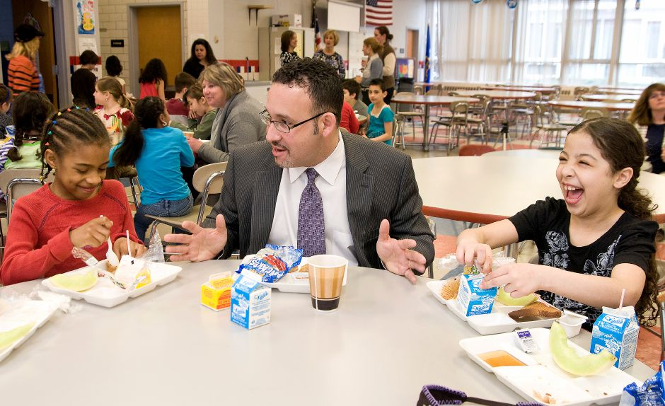 "Miguel Cardona, principal of Hanover School, eats breakfast and talks about Justain Bieber with third graders Asharia Ray (left) and Dina Hamideh (right) in the school cafeteria in Meriden, April 1, 2011. ""I enjoy spending time with the students,"" said Cardona. ""This is just a happy place to be."" (Sarah Nathan/ Record-Journal)"