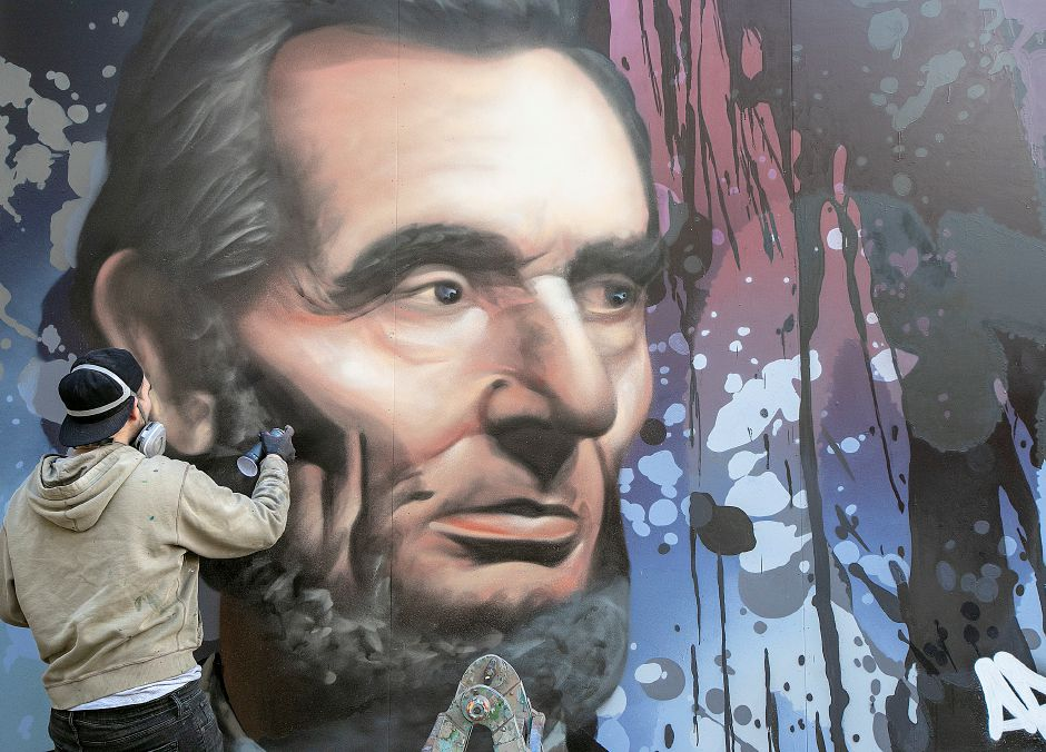 "Global graffiti artist ""ARCY,"" of North Haven, spray-paints a portrait of Abraham Lincoln on a large canvas outside Lincoln Middle School in Meriden Monday. ARCY is known for his large-scale art. Watch the video, and find more photos at myrecordjournal.com. Photos by Dave Zajac, Record-Journal"