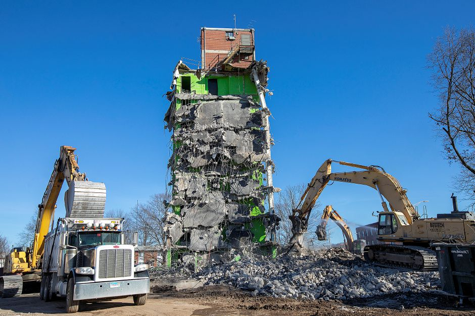 Demolition crews clean up the area around one of the last standing structures of the former Mills Memorial Apartments, Wednesday., Dec. 19, 2018. Dave Zajac, Record-Journal