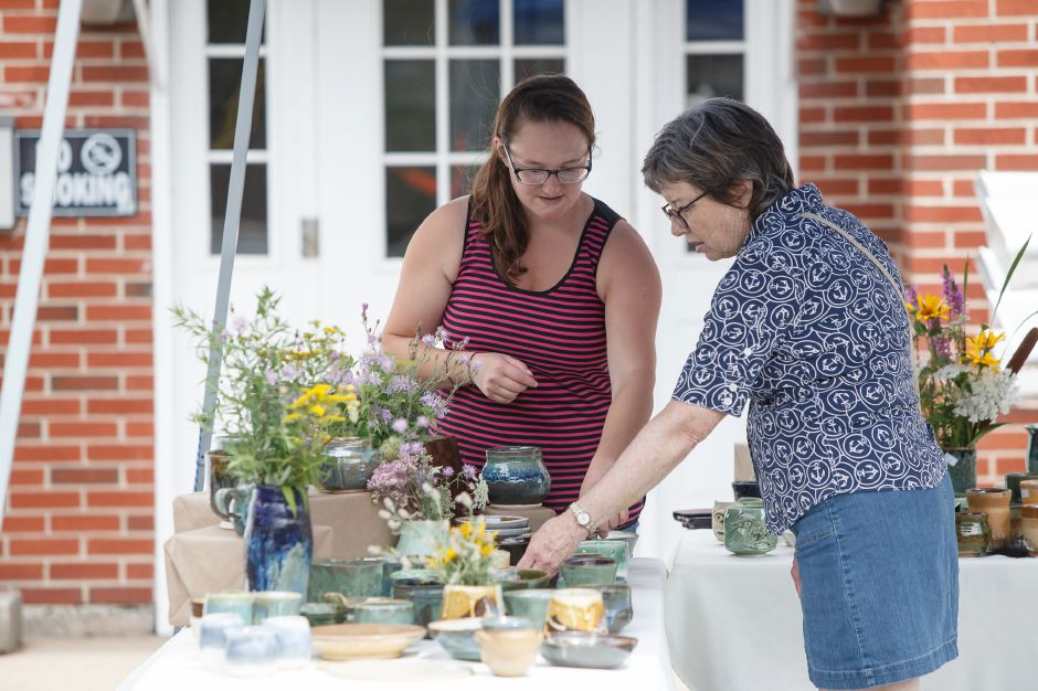 Jen Baker left of Southington talks about her pottery work with Diane McDonald of Southington Sunday during a Summer Sidewalk Sale at Southington Community Cultural Arts Center in Southington July 22, 2018 | Justin Weekes / Special to the Record-Journal