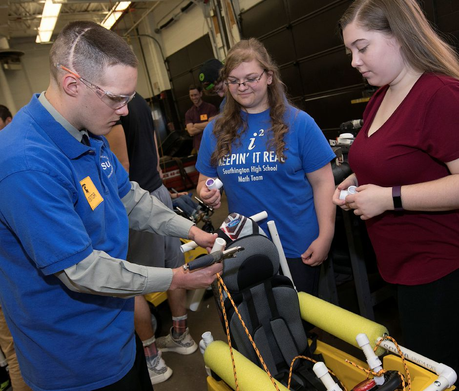 Central Connecticut State University student, Gary Liseo, left, and Southington High School students, Rebecca Dorzens, 17, center, and Sydney Bradshaw, 17, right, work on a modified battery-powered car for one of two special needs children at Southington High School Friday, May 11, 2018. Dave Zajac, Record-Journal