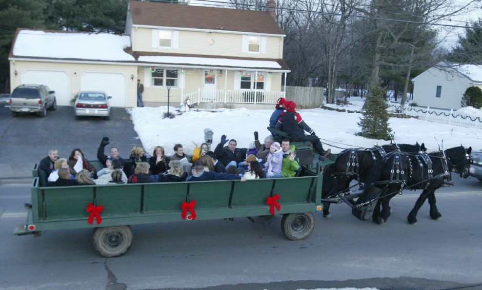 Members of the Salvatore/Simone family sing Christmas carols while they ride in the horse drawn wagon from Wood Acres Farm of Terryville down Pleasant Street in Southington on Dec. 17, 2005.