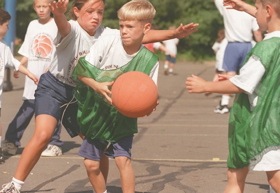 RJ file photo - Mike Bush, 8, of Wallingford tries to drive around a defender and toward the hoop during morning action at the Hoop House Basketball Camp run by the town Aug. 12, 1998.