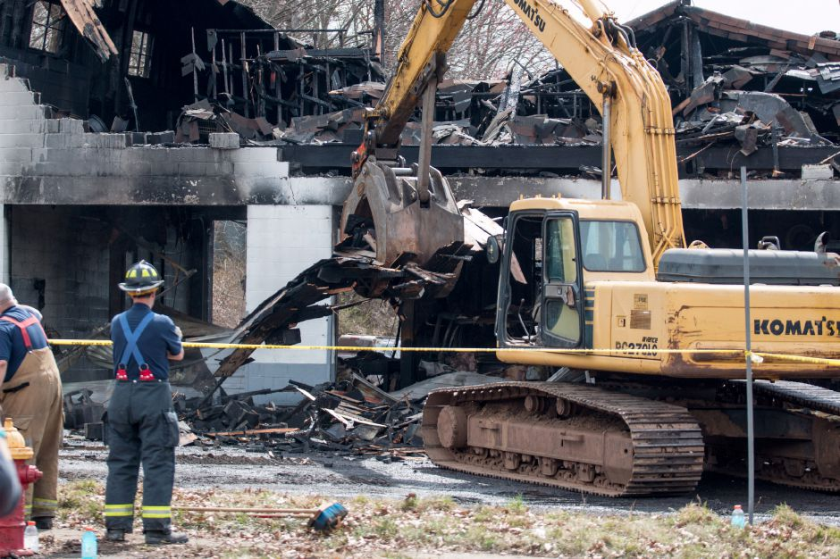 A fIrefighter observes as an escavator removes desbris left by a fire at 45 Hall Avenue in Meriden on Friday, April 13, 2018. The building, home to J.C. Recycling Inc., was deemed a total loss. | Devin Leith-Yessian/Record-Journal