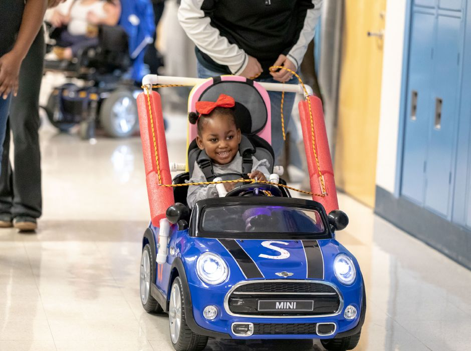 Sanae Green, 3, of New York City, test drives a toy car built for her by Plainville middle and high school students and Central Connecticut State University technology education students. Organized by the Go Baby Go program, the students retrofitted four cars for children with limited mobility on Dec. 7 and 8, 2018. | Devin Leith-Yessian/Plainville Citizen