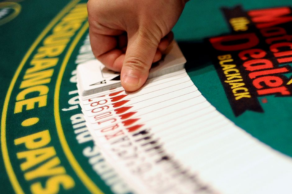 In this Sept. 18, 2013, photo, a dealer demonstrates a card fan at a blackjack table at Mohegan Sun in Uncasville, Conn. (AP Photo/Jessica Hill)