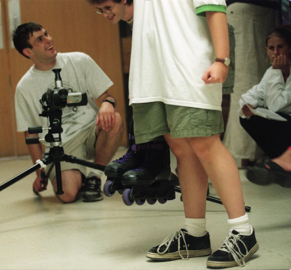 Eric Forand, left, and Matt Baume, center, get set to film a scene involving students with rollerblades and skate boards in the hallway of Southington High, Aug. 1999 . Holding a pair of skates is Marissa Brookes.